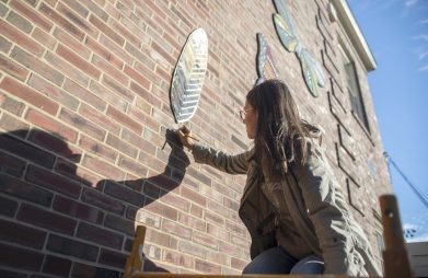 Artist Danielle Casali marks out where one of the colorful mosaic mural elements should be positioned on the south wall of Hollywood School in Brookfield on Oct. 19. The new artwork, which overlooks the school's butterfly garden is the result of a collaborative art project between Casali and students last spring. The project was funded by the school's PTA. (Alex Rogals/Staff Photographer)