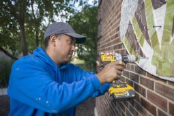 Luis Gonzalez hangs up one of the mosaics on Saturday, Oct. 19 at Hollywood Elementary School in Brookfield, Ill. (ALEX ROGALS/Staff Photographer)
