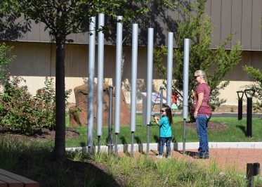 """Surrounding the Hamill Family Nature Plaza are gardens featuring native plants and interactive elements like giant chimes, a council ring and a fabricated """"nest."""""""