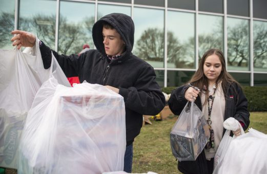 Ryan Gaynor, left, an RBHS senior from Riverside, and Gia Diaz, a sophomore from North Riverside, drop off bags of toys at the donation table on Dec. 13, during a toy drive at the WGN Studios in Chicago. | ALEX ROGALS/Staff Photographer