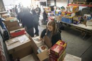 Volunteers pack up food and supplies for families in need on Dec. 22, at Twilight Party Rentals in Brookfield. | ALEX ROGALS/Staff Photographer
