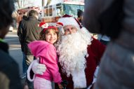 Marie Dudzik, 6, of North Riverside, snuggles up to Santa for a photo on Dec. 21 during his annual tour through North Riverside aboard one of the village's fire trucks. Santa made nearly a dozen stops that morning on his way to Caledonia Senior Living and Memory Care. | SHANEL ROMAIN/Contributor