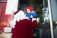 D.J Krubl, 4 of North Riverside being lifted out of the fire truck by Santa on Saturday. Dozens of families were greeted with sirens and Santa Clause throughout North Riverside. | SHANEL ROMAIN/Contributor