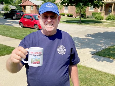 Tony Novak holds up one of the 89 mugs he and his neighbors funded and presented to North Riverside village employees as a thank you and a memento of the work they did during the COVID-19 crisis. (Provided)