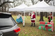 From left, Elizabeth Nelson-Sifuentes, Ron Malchiodi and Megan Siska, wave to motorists on Dec. 12, during a drive-by Santa event outside of Scout Cabin in Riverside.