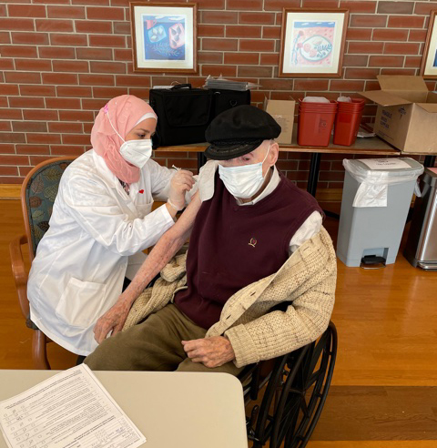 A Cantata Adult Life Services resident receives his COVID-19 vaccination from a CVS pharmacy employee on Jan. 2. (PROVIDED)