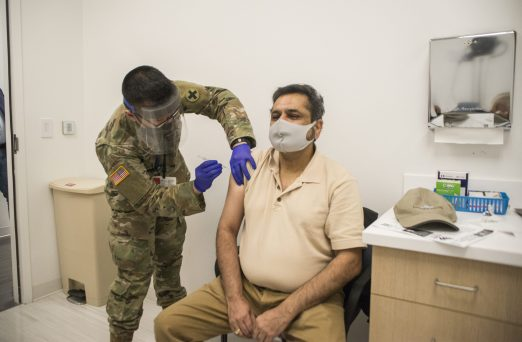 US Army Illinois National Guard specialist Sean Sumugat gives the first dose of the COVID-19 vaccine to Jay Trivedi on Jan. 22, 2021, at the Cook County Health's North Riverside Health Clinic. (Alex Rogals/Staff Photographer)