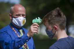 Brook Park principal Mike Sorensen, left, takes a student's temperature with a decorated thermo-gun before being allowed to enter the building on Sept. 21 in LaGrange Park. (Alex Rogals/Staff Photographer)