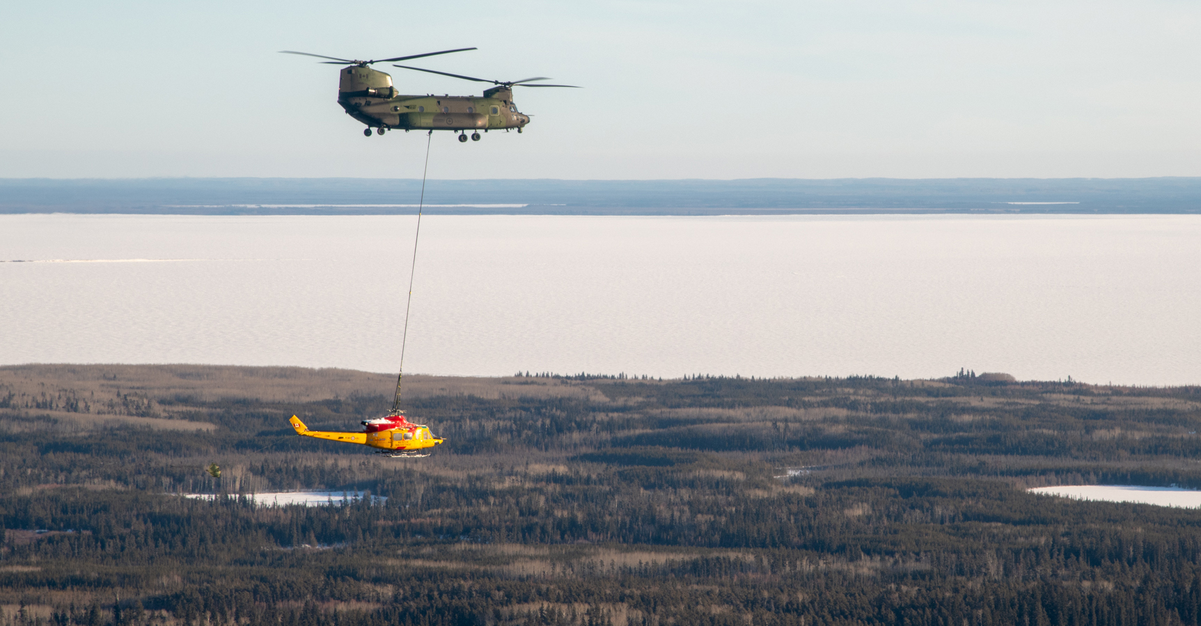 hight resolution of a large helicopter in flight with a smaller helicopter suspended below it attached by