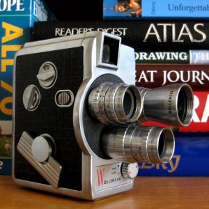 Photograph of movie camera with travel books in the background