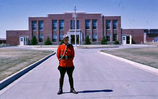 """June 1966 - Photograph of Constable Gordon Lastucka standing in red serge in front of the third Riding School at """"Depot"""" Division (Source of photo - Ric Hall's Photo Collection)."""