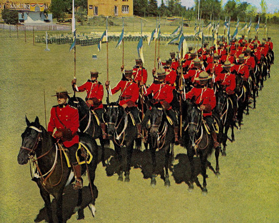 Photograph of RCMP Musical Ride members with blue and yellow pennons (Source of photo - Ric Hall's Photo Collection)