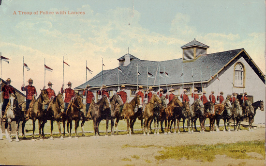 Photograph of RNWMP members at Depot with the horse stables in the background (Source of photo - Ric Hall's Photo Collection).