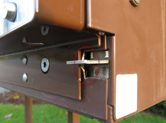 Photograph of a Canada Post Super Mail Box that has been compromised.  The red circle shows where the culprits inserted a bar to bypass the lock mechanism. (Source of photo - Sheldon Boles)