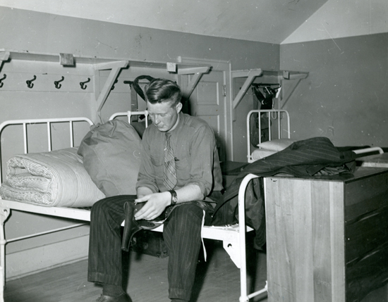 "Photograph of a RCMP recruit sitting on his bed in ""B"" Block at Depot Division in Regina (Source of photo - Ric Hall's Photo Collection)."