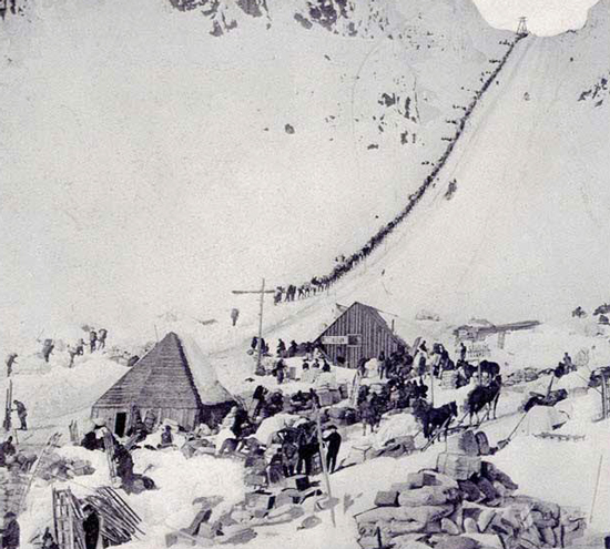 1898 - Photograph of the Chilkoot Pass with gold miners carrying their packs up to the summit.