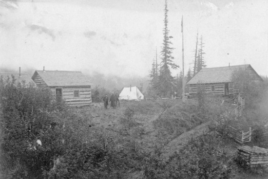 """1898 - Photograph of the cabins and tent camp of the NWMP t Stikine River.  Members in the photograph are Supt. Primrose and Comp. H.J. Woodside (Source of photo - RCMP Historical Collections Unit - """"Depot"""" Division)."""