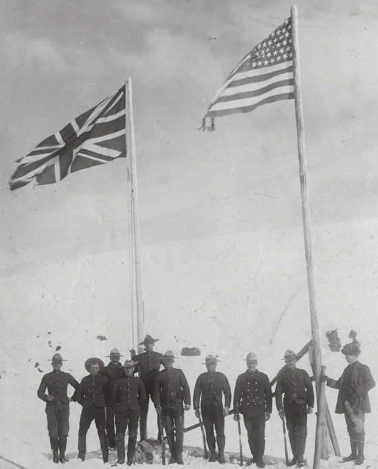 """Photograph of the White Pass Summit :the United States & Canada boundary line with flags of each country.  Members of NWMP in the photograph (Source of photo - RCMP Historical Collections Unit - """"Depot"""" Division)"""