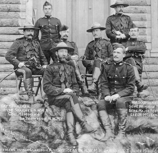 """June 1900 - Photograph of  Dawson NWMP Officers. Right side: Insp. Scarth, Supt. Primrose, Sergt. Major Fost, Lieut McLean; Left: Insp. Starnes, Col. Hemmins, Dr. Thompson (Source of photo - RCMP Historical Collections Unit - """"Depot"""" Division)."""
