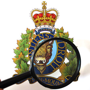 Photograph of RCMP crest with a magnifying glass