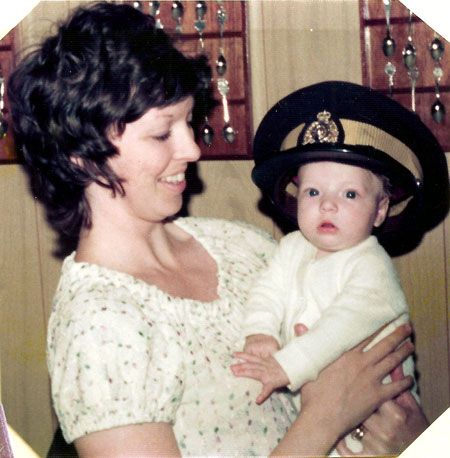 Photograph of mother holding baby who is wearing a RCMP forage cap (Source of photo - Ric Hall's Photo Collection).