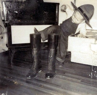 Photograph of a young member's son trying on those tall boots that dad always wore (Source of photo - Ric Hall's Photo Collection).