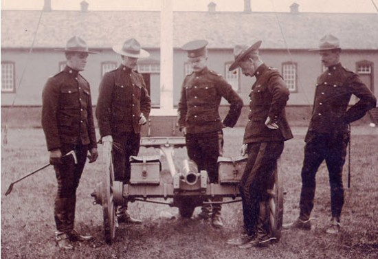 """Photograph of RNWMP members at Prince Alberta Post viewing their 7-pounder artillery piece (Source of photo - RCMP Historical Collection - """"Depot"""" Division)."""