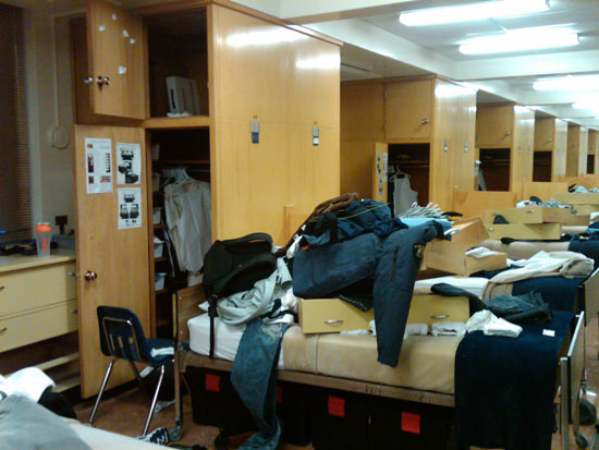 """Photograph of a RCMP """"Depot"""" Troop Dorm which didn't have their kit laid out as outlined not as per instructions.  Note in the photograph - the laying out of kit is illustrated on the inside of the closet door (Source of photo - Ric Hall's Photo Collection)."""