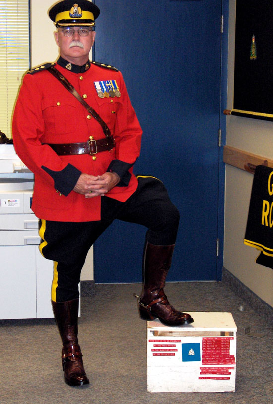 Photograph of retired Supt. Ric Hall in red serge with his foot upon the