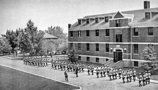 "1937 - Photograph of RCMP  recruits marching in formation past ""C"" Block at ""Depot"" Division in Regina (Source of photo - RCMP Quarter 1937)"