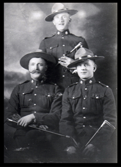 Photograph of three handsome RCMP members.  Corporal Arthur Barker is standing in the rear. (Source of photo - Ric Hall's Photo Collection).