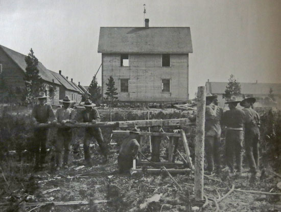 "1902 - Photograph of NWMP members at Whitehorse moving a building at their new ""H"" Division Headquarters."