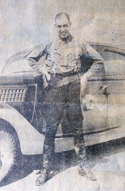 Photograph of Corporal Tom Raisbeck standing by his car (Source of photo - Ric Hall's Photo Collection).