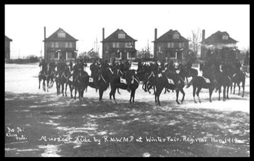 "1919 - Photograph of RNWMP Musical Ride at ""Depot"" Division on the Parade Square with white blankets.  Officer's residence in the background. (Source of photo - Ric Hall's Photo Collection)."
