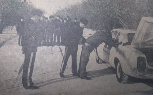 Photograph of S/Sgt. H.T. Laing searching a 'suspect.'