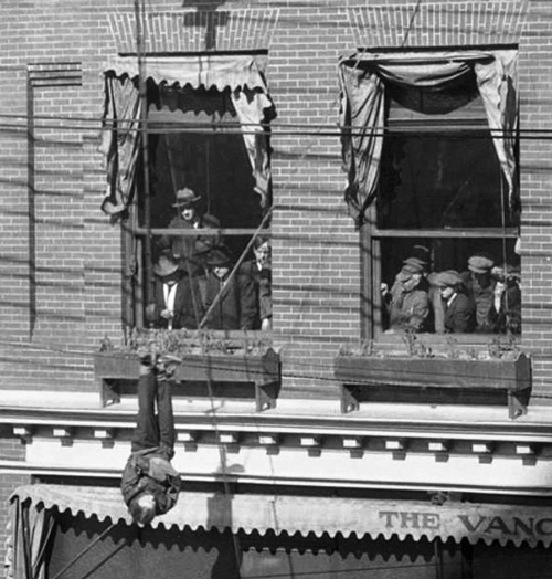 Photograph of Harry Houdini hanging from a 3rd floor outside the Vancouver Sun newspaper office (Source of photo - City Vancouver Archives)