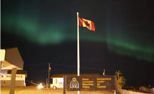 Photograph of an RCMP Detachment with the Canadian flag with the northern lights in the background (Source of photo - Ric Hall's Photo Collection).