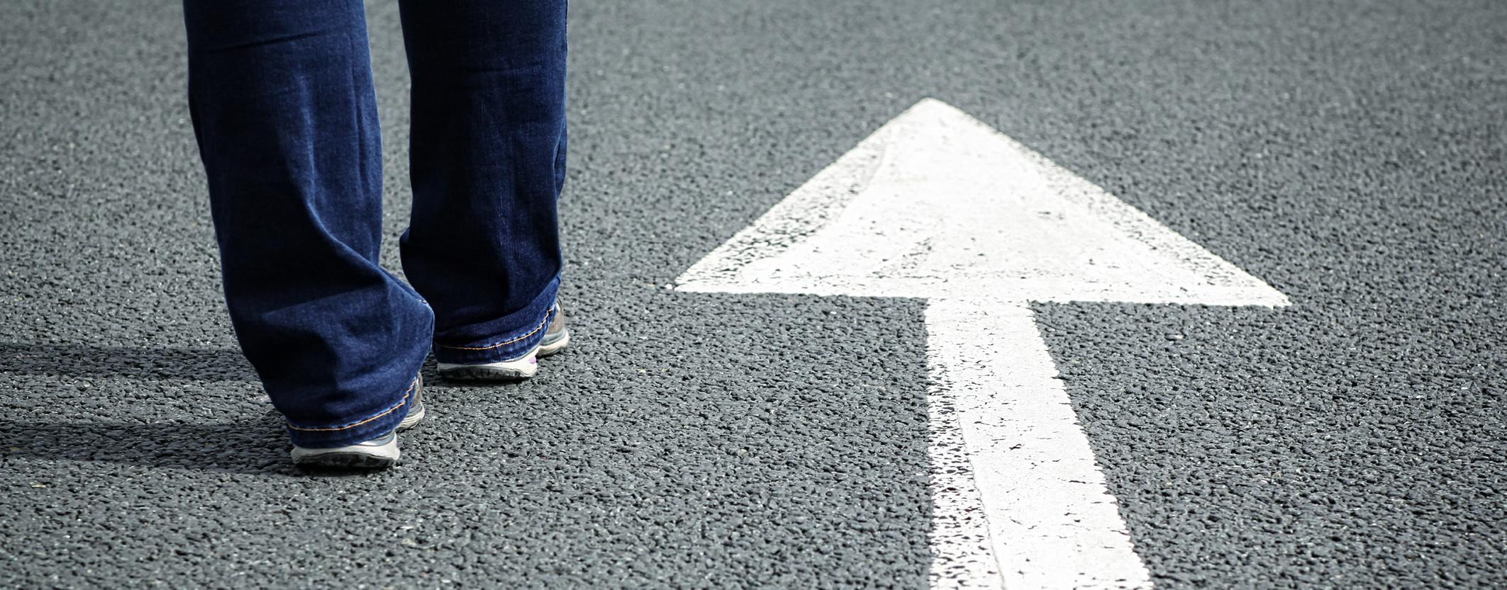 feet walking on road with white arrow