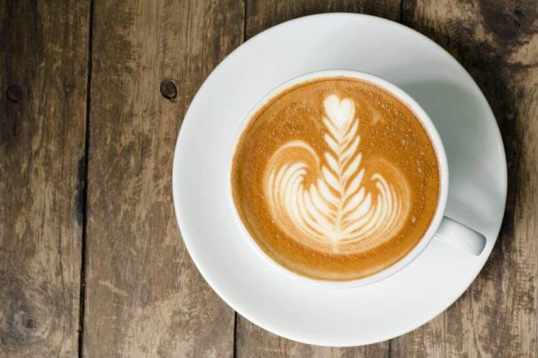 Latte art on dark grained wood top view
