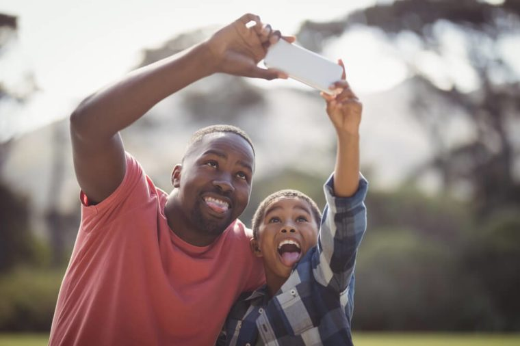 Father and son taking selfie with mobile phone on a sunny day