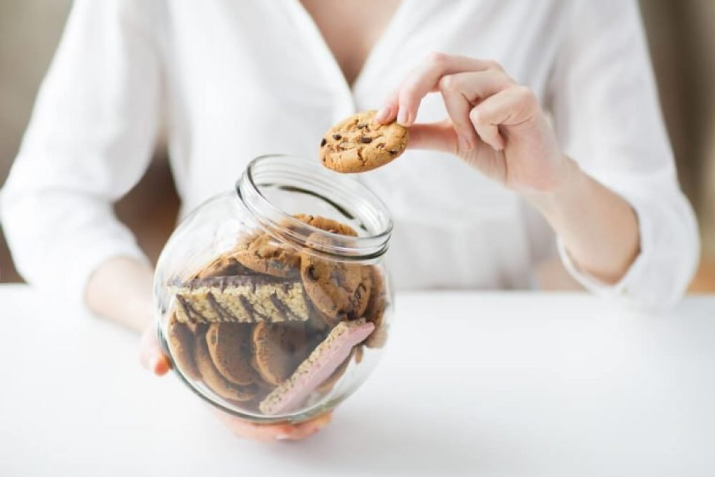 people, junk food, culinary, baking and unhealthy eating concept - close up of hands with chocolate oatmeal cookies and muesli bars in glass jar
