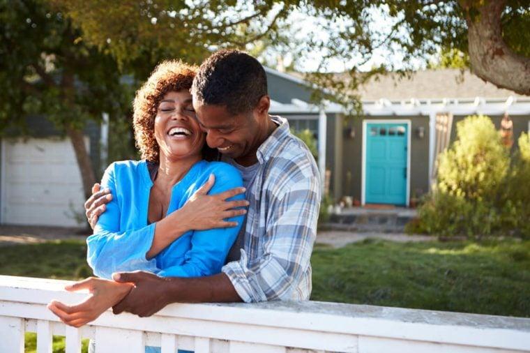 Mature Couple Leaning On Back Yard Fence