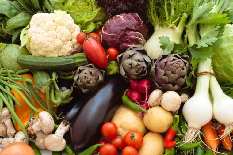 Background of mixed fresh organic vegetables and herbs.