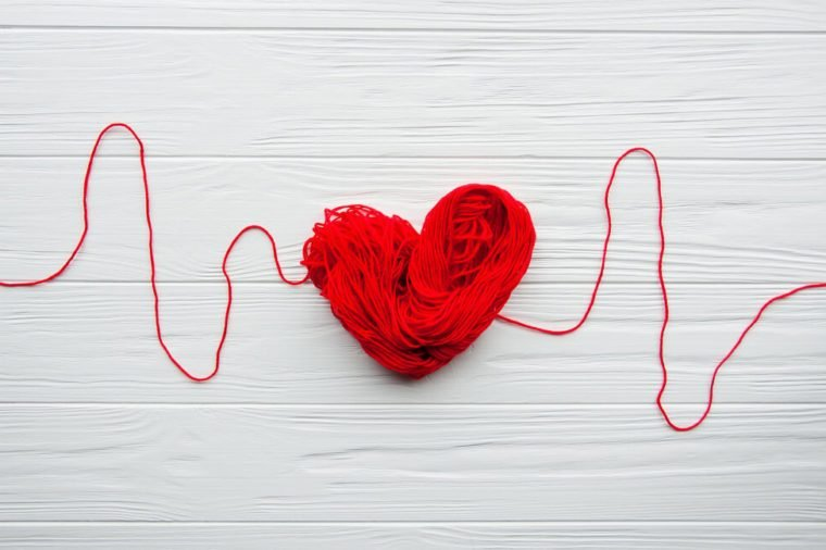 Health, medicine, people and cardiology concept. Abstract red heart. Problems with heart. Heart and cardiogram is made of red thread.