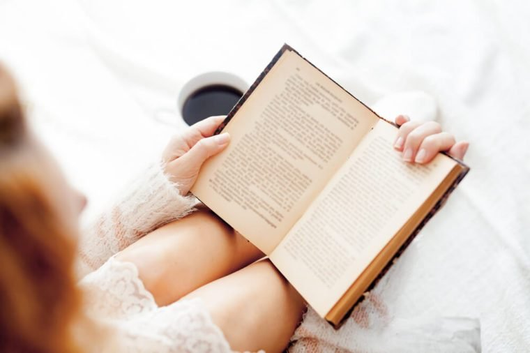 Soft photo of woman reading a book on the bed