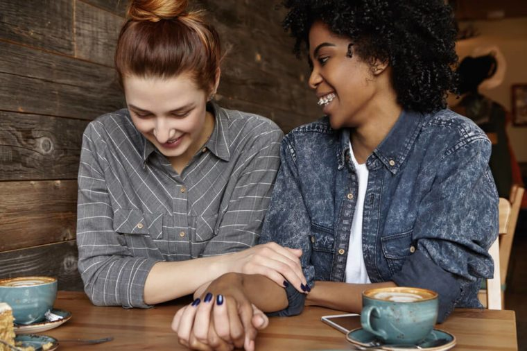 Love and relationships. Cheerful African lesbian with braces and Afro hairstyle holding hands with her cute redhead girlfriend, talking to each other at cafe, sharing happy and sweet moments together