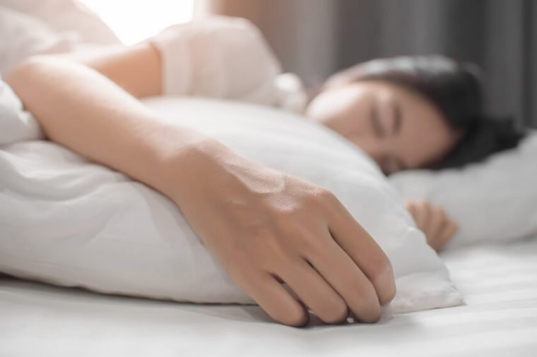 Cute girl on a soft white bed. She sleeping and relaxing.