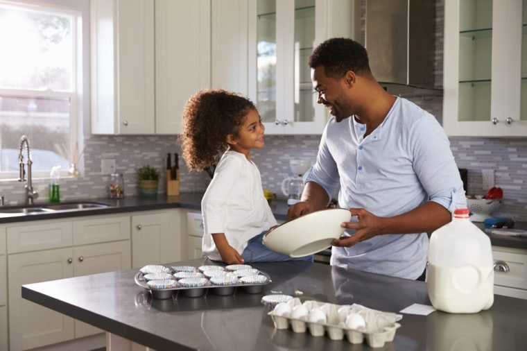 Black dad and young daughter look at each other while baking