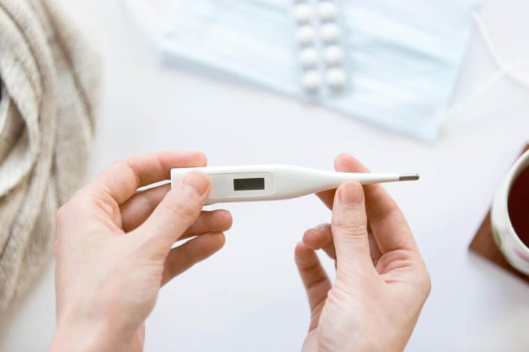 Female hands holding an electronic thermometer over the white office desk. View over the shoulder, medicine concept photo. High angle view