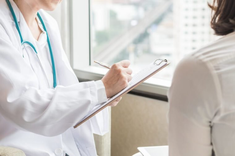 Doctor (gynecologist or psychiatrist) consulting and diagnostic examining woman patient's health in medical clinic or hospital healthcare service center